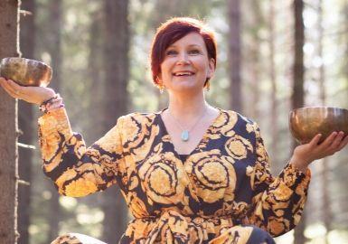 Pinja Kaisko hymyilee metsässä keltaisessa mekossa äänimaljat kädessä.