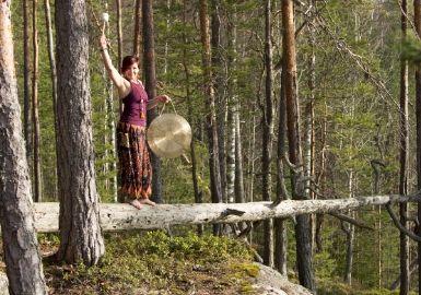 Pinja Kaisko lyö gongia metsässä kelon päällä seisten.