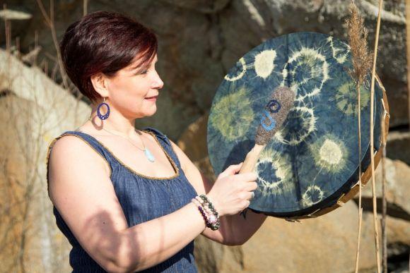 Pinja Kaisko lyö rumpua sinisessä mekossa auringossa kalliolla