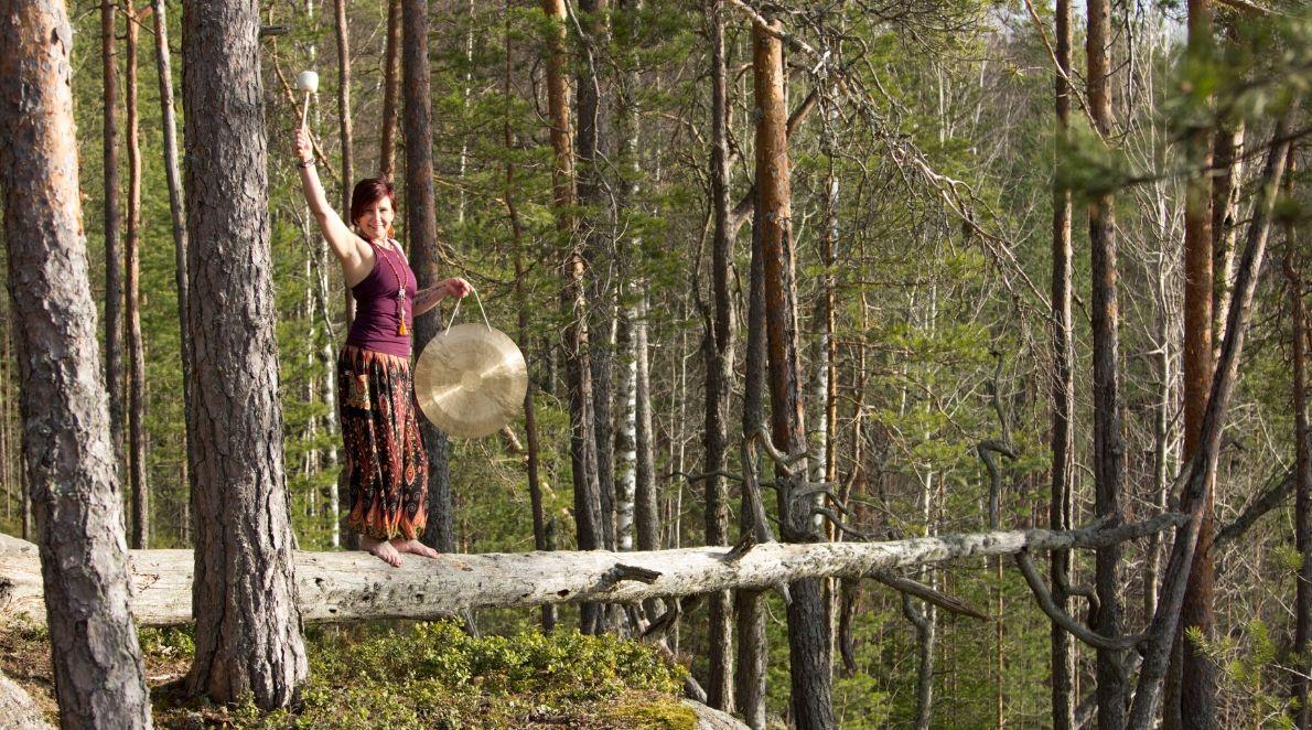 Pinja Sointu esittelee äänimaljahoitoihin kuuluvaa gongia metsässä.
