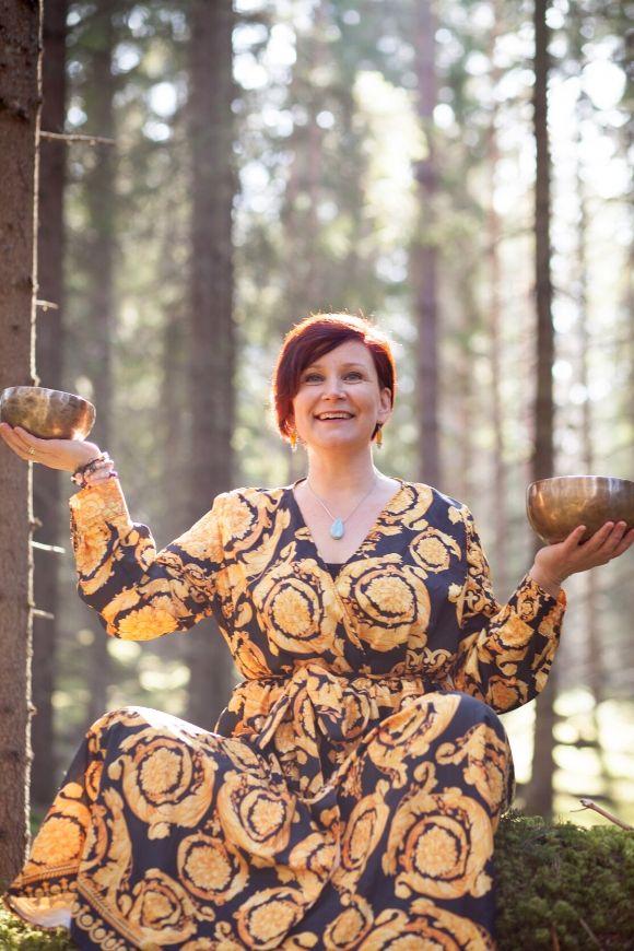 Äänimaljahoitaja Pinja Kaisko istuu sammalmetsässä pidellen äänimaljoja.