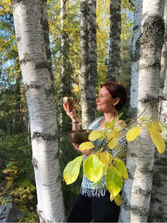 Pinja Sointu metsässä äänimaljarentoutuksen parissa.