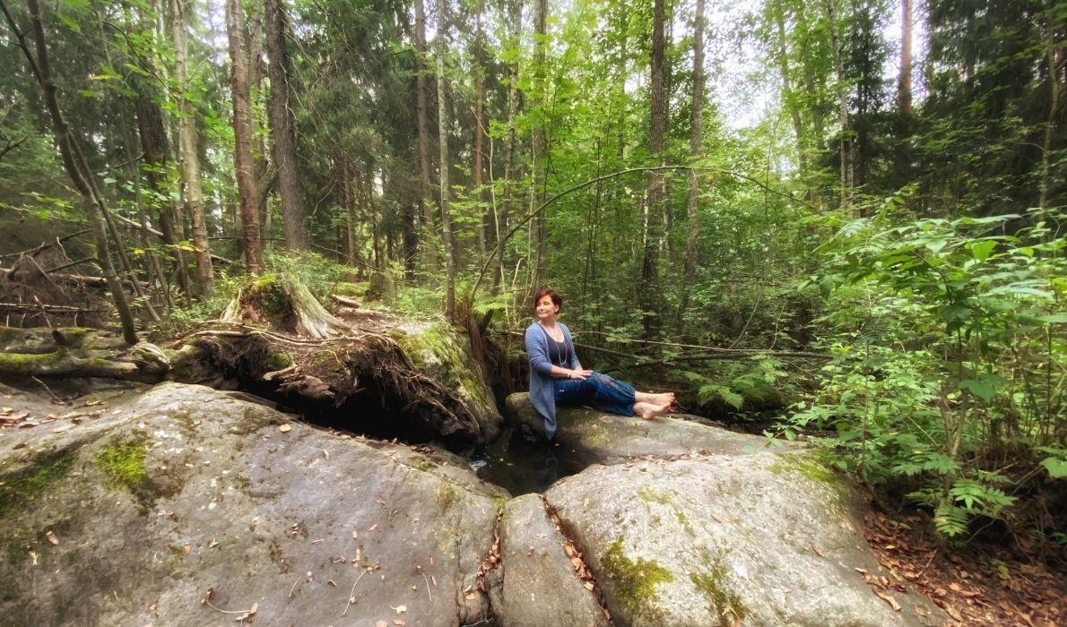 Pinja Kaisko istuu hymyillen kallion päällä metsässä.