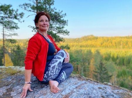 Pinja Kaisko joogaa kalliolla auringossa.