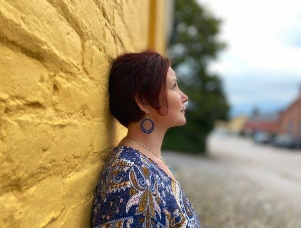 Pinja Kaisko nojaa keltaista seinää vasten.